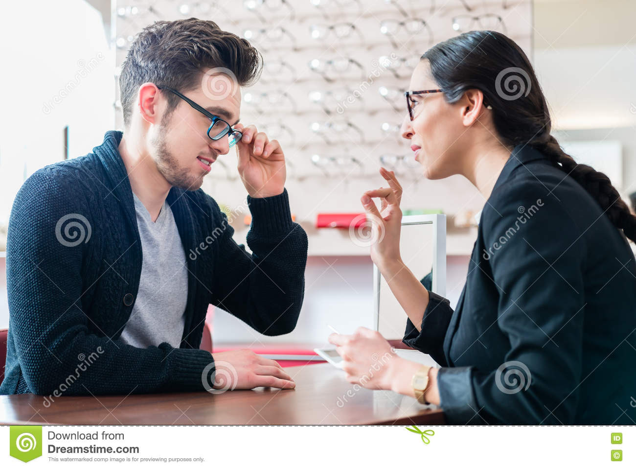 368150d29b Man in optician shop getting advice from saleswoman buying new glasses