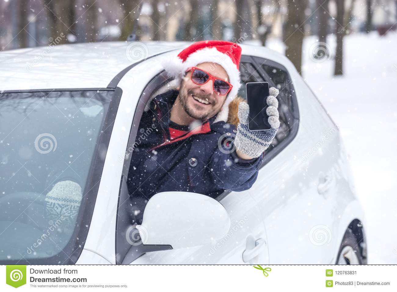 86c295754c706 Man out of car window wearing Santa Claus hat and holding blank screen  smart phone.