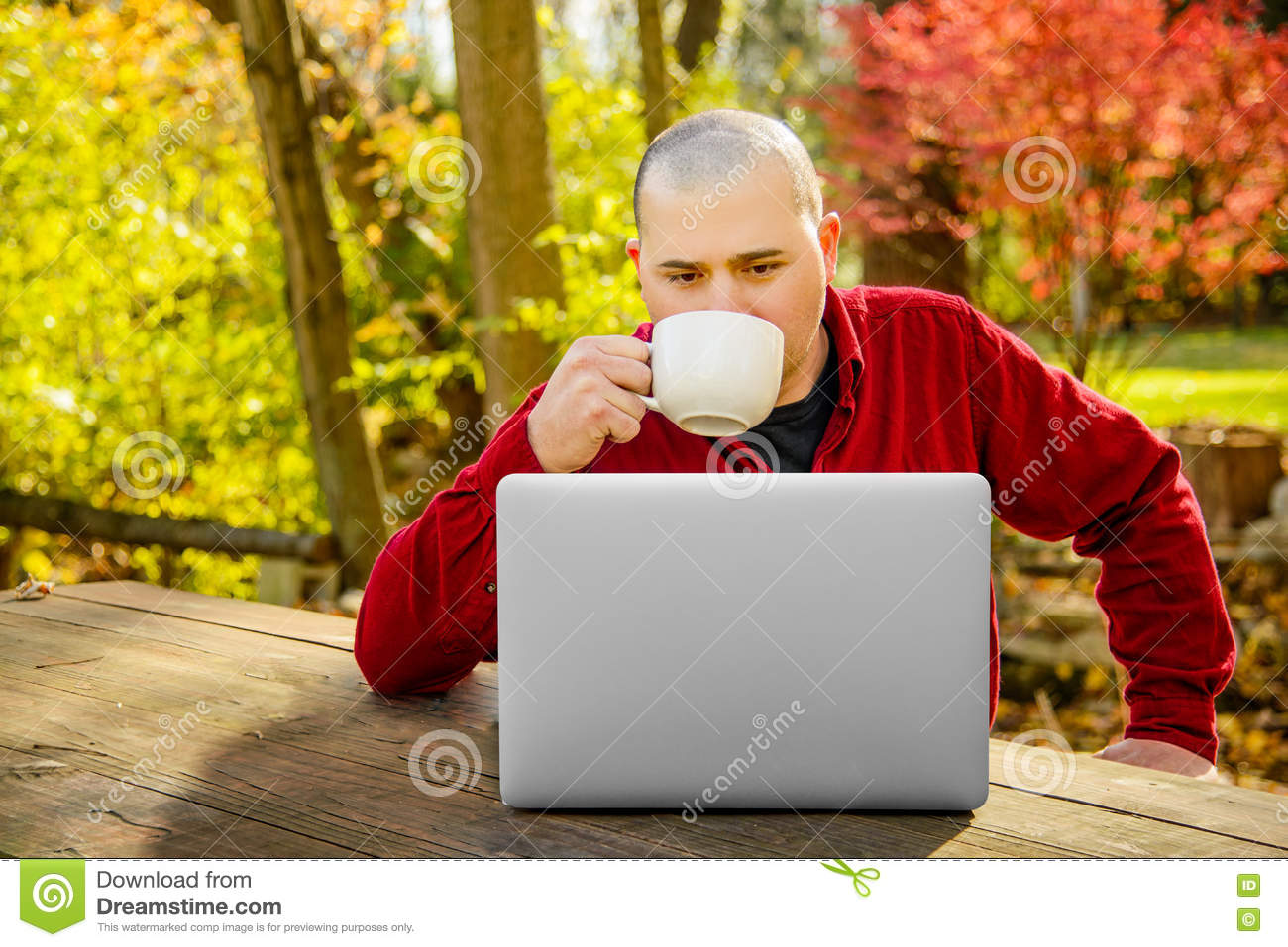 Man outdoors looking at Laptop and Drinking Coffee