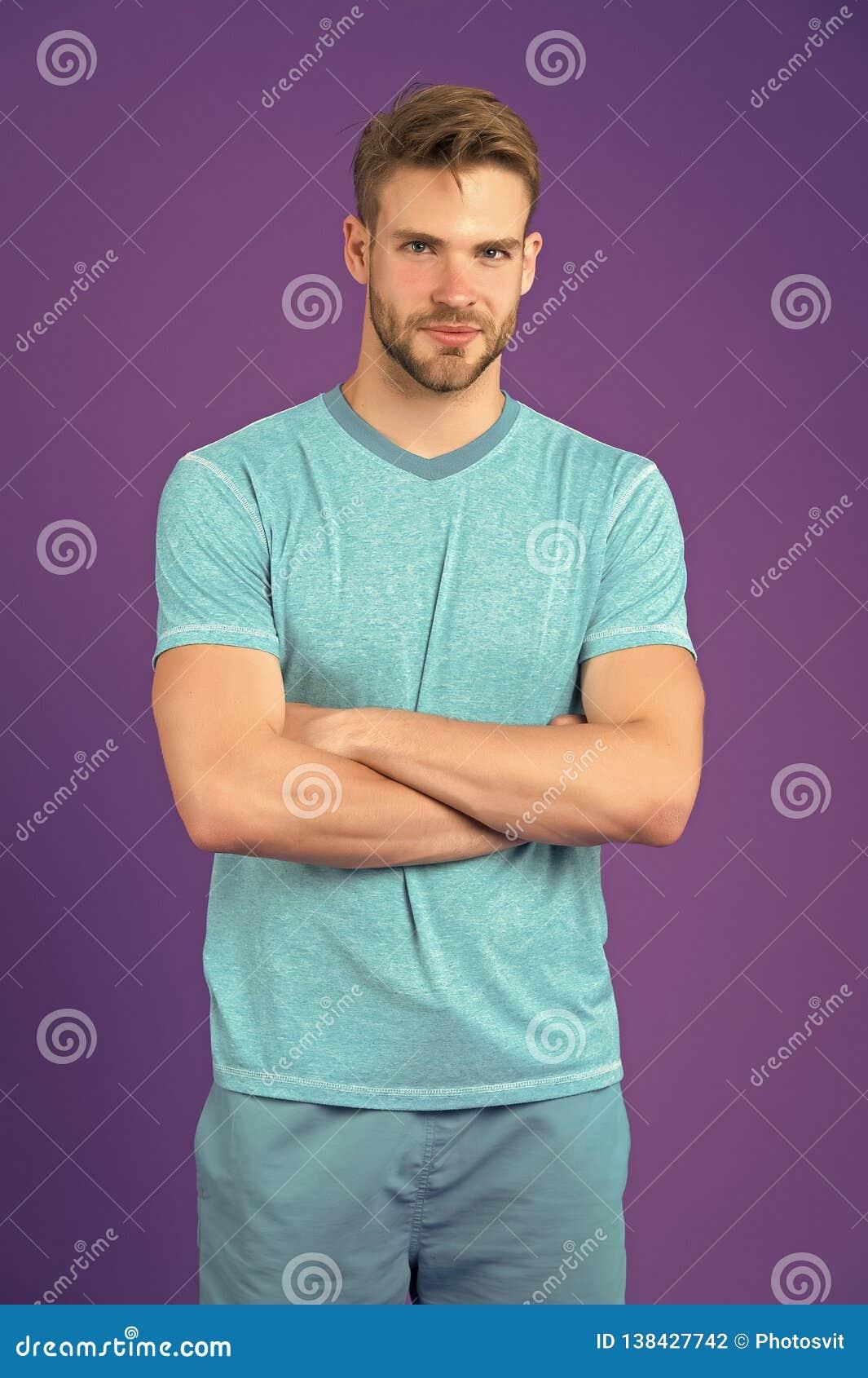 Man på att le framsidan som säkert poserar med vikta armar, violett bakgrund Grabben med borstet bär uppsättningen av sportive