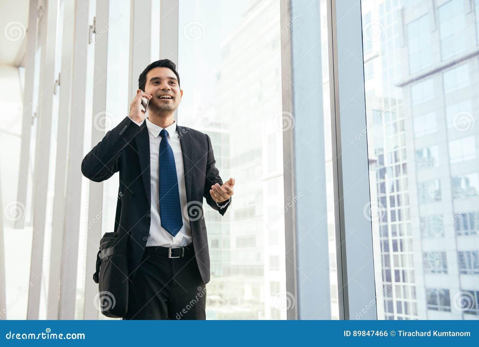 Man på den smarta telefonen - ung affärsman i flygplats Tillfällig stads- yrkesmässig affärsman som använder att le för smartphon