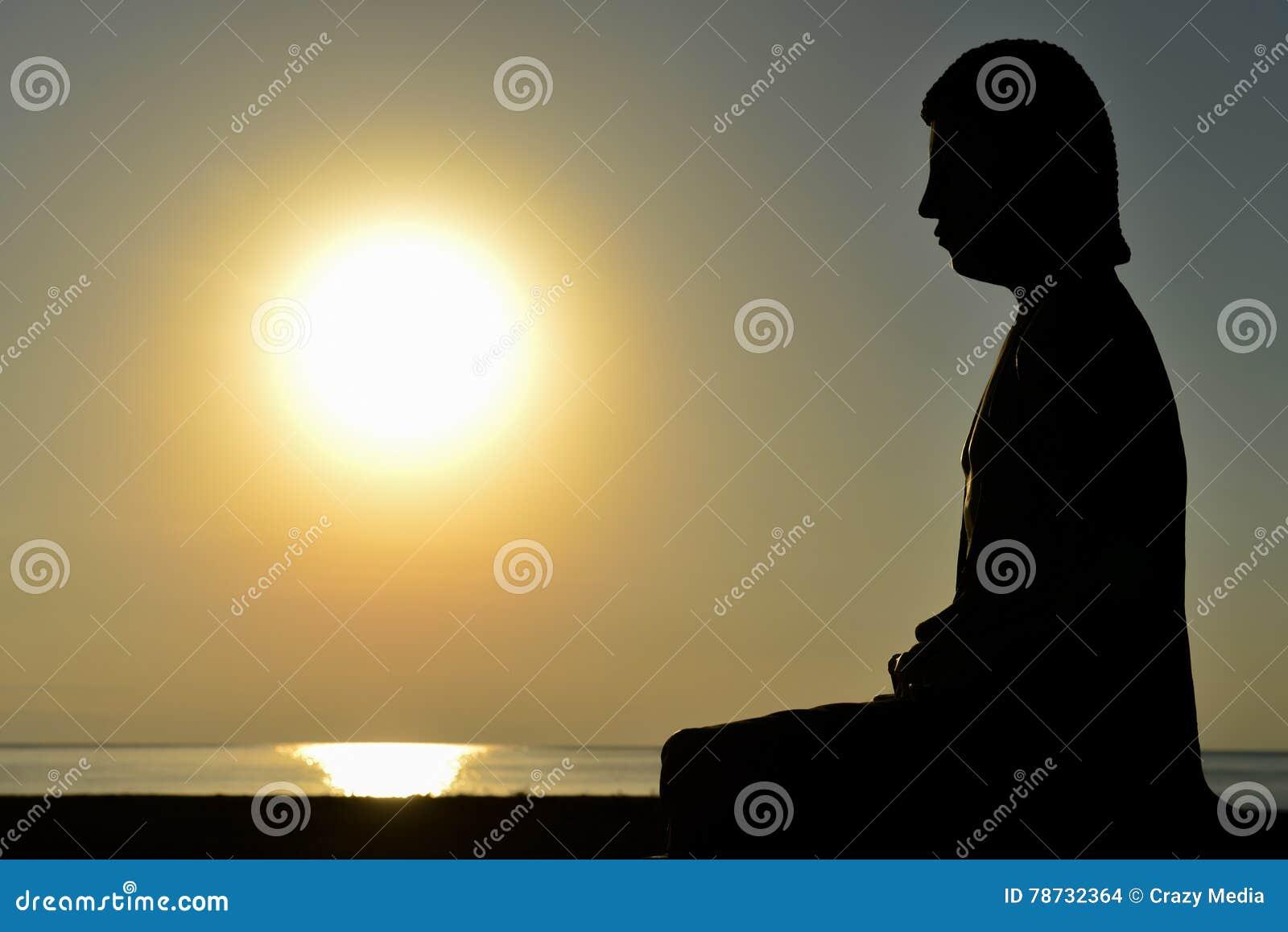 Man på sjösidan som gör yoga på solnedgången