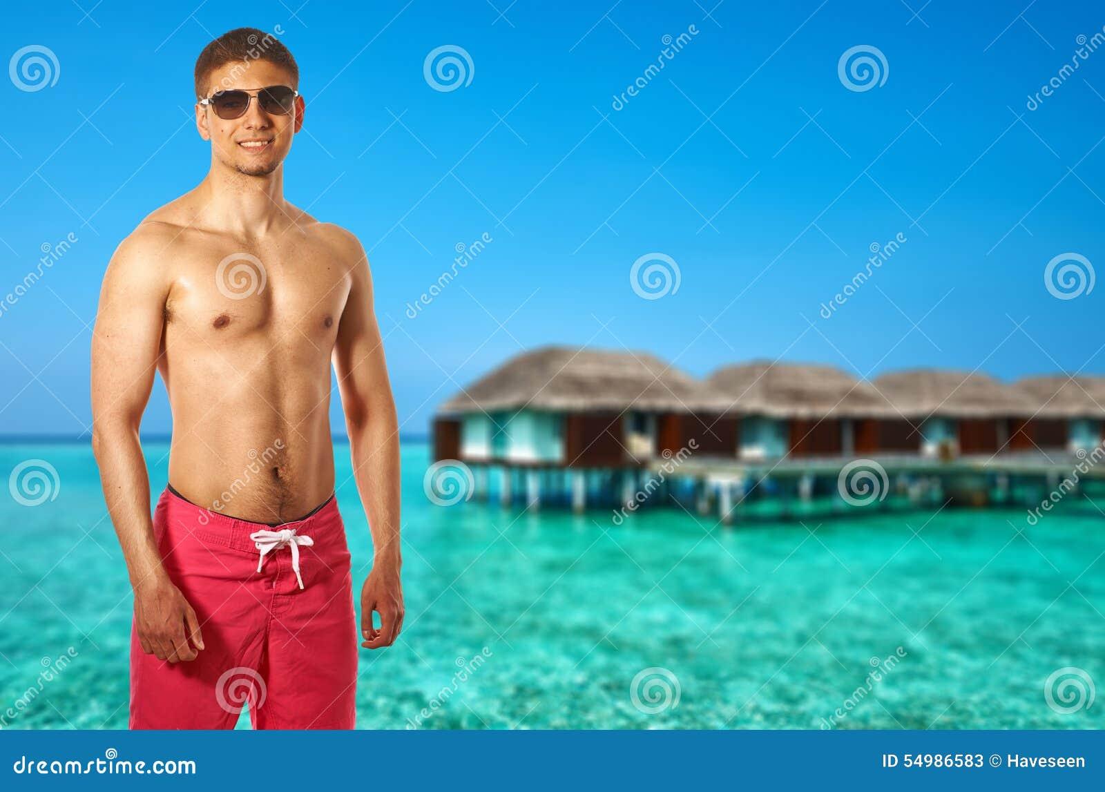 Man på stranden med vattenbungalower
