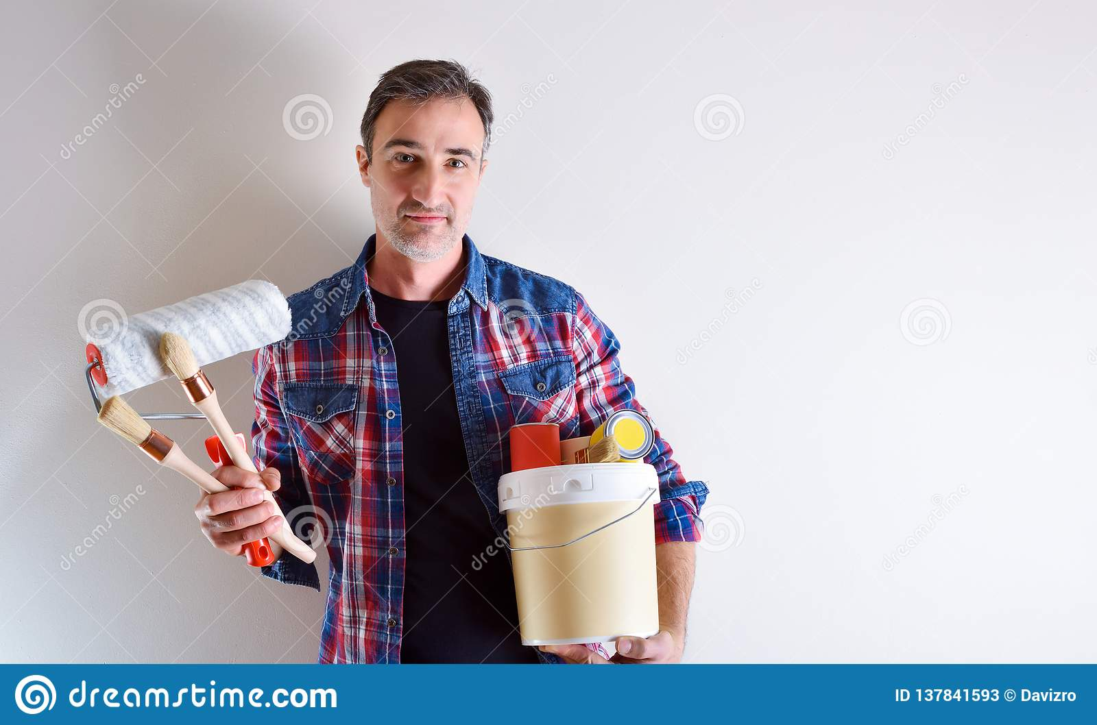 Man with paint tools on hands and white wall behind