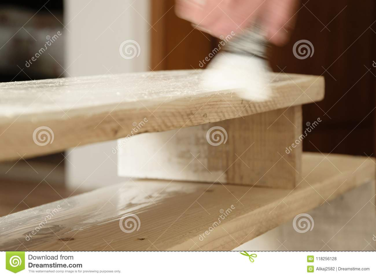Man paint with white colore wooden plank indoors