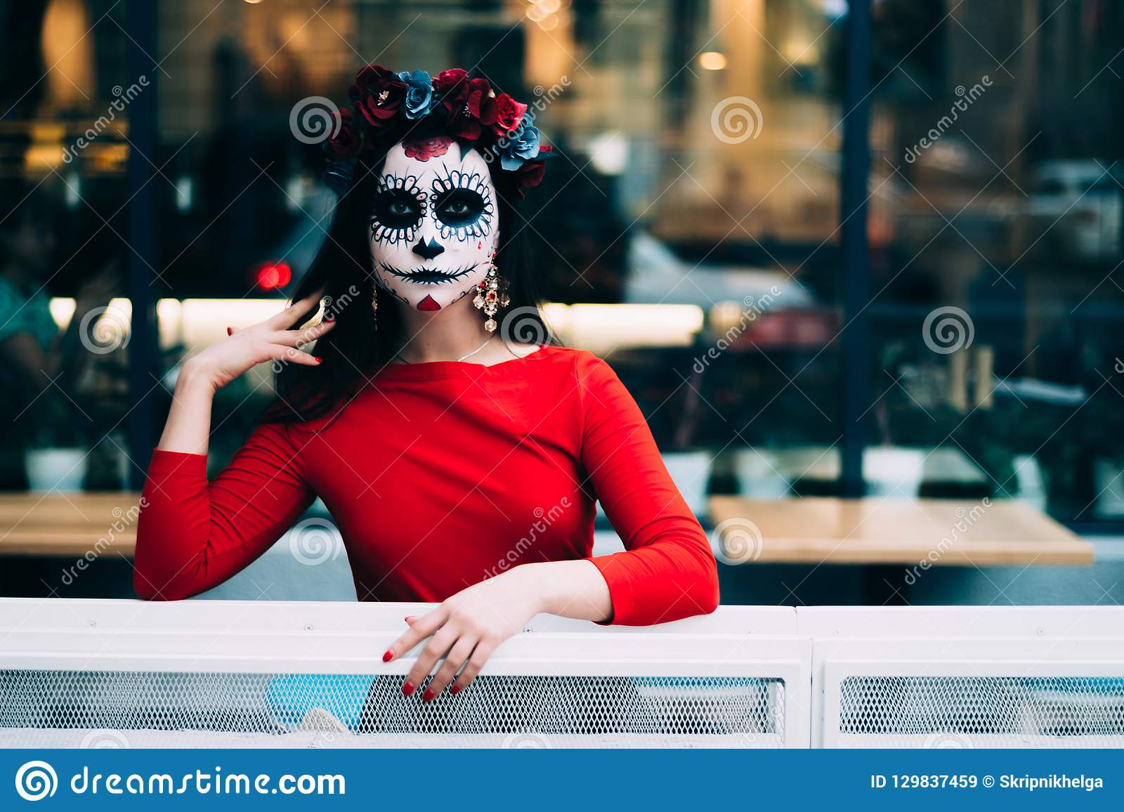 A man with a painted face of a skeleton, a dead zombie, in the city during the day. day of all souls, day of the dead, halloween,