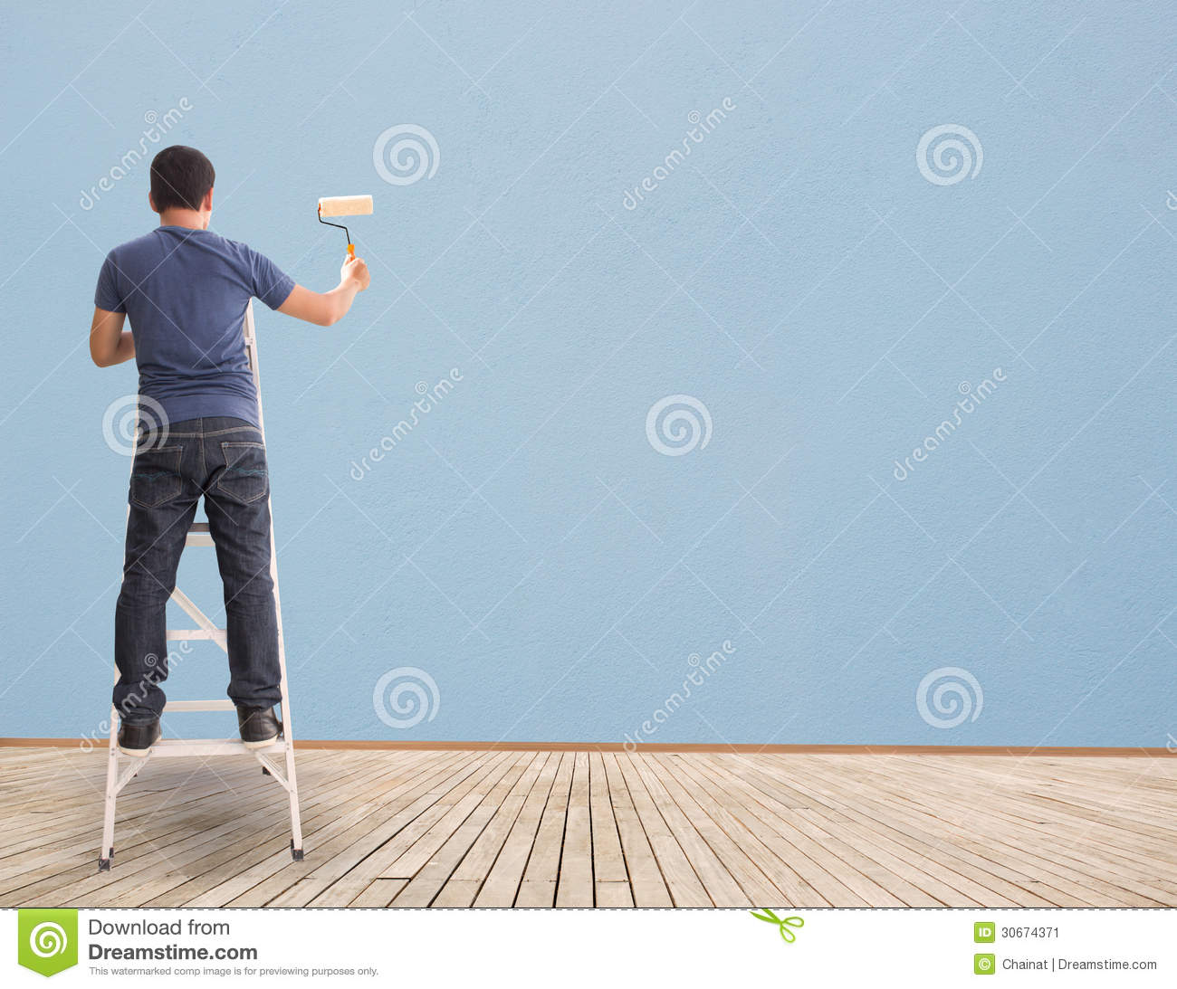 Person painting wall - Man Painting On Blue Blank Wall Stock Image
