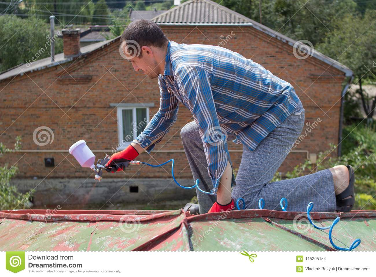 A man paints a roof stock photo  Image of compressor - 115205154