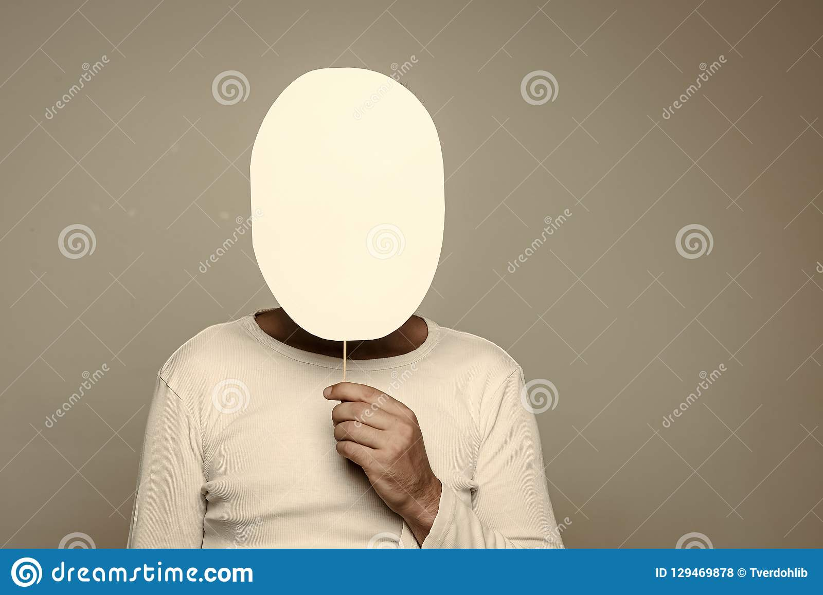 man with paper nameplate hiding face on grey background stock photo