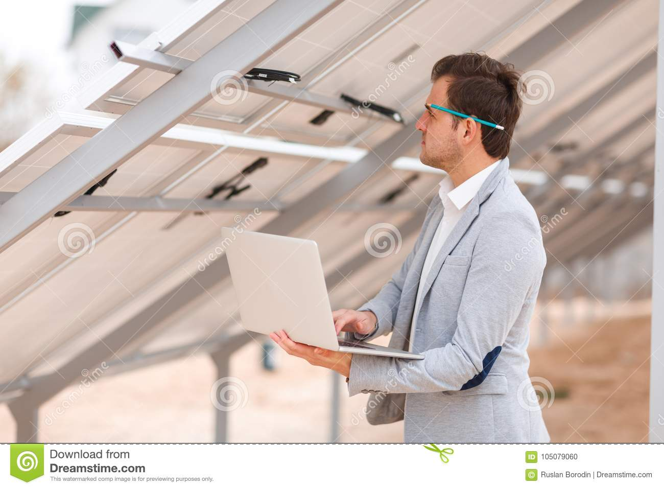 A Man With Pencil Behind His Ear Holds Laptop And Looks At The Wiring Harness Installed Solid In Suit Modern Hands For Solar Panels On