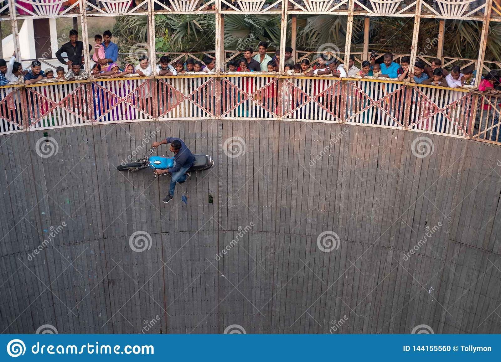 A man performs stunts while riding the wall of death at a festival surrounding NAN