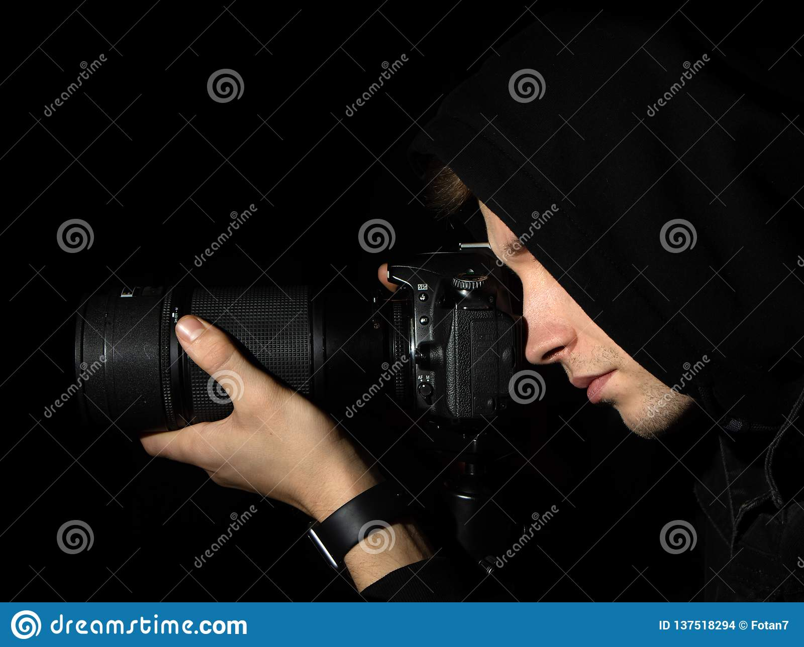 Man photographer with a DSLR camera on a tripod in a black hood isolated black background