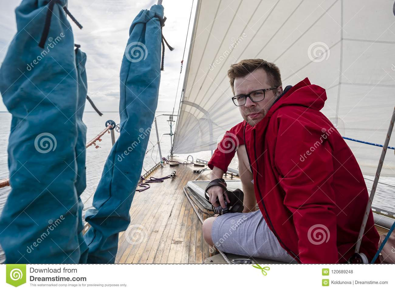 A Man - A Photographer In A Red Jacket And Glasses Sits On The D