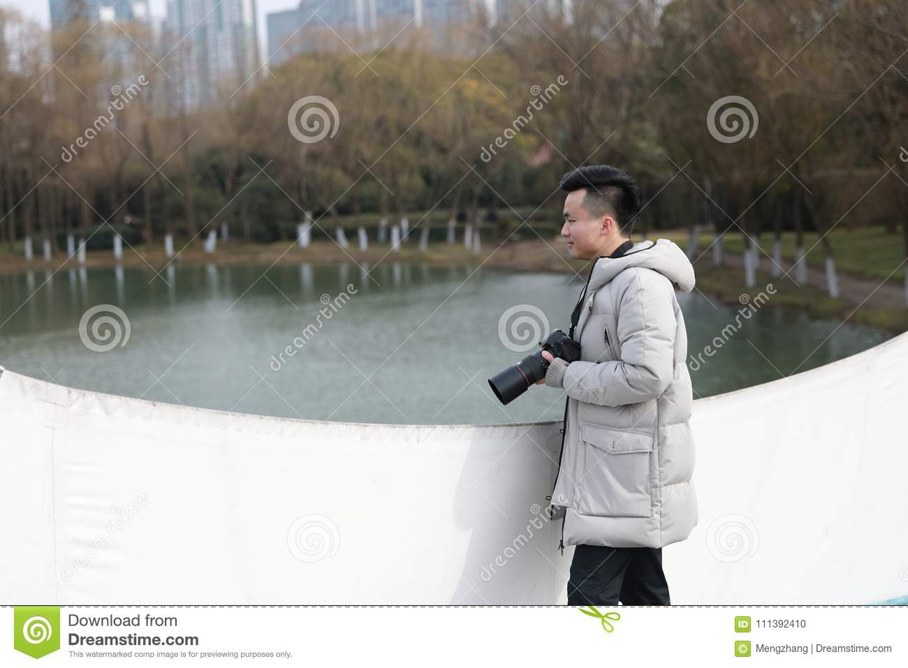 Asian chinese man photographer in park
