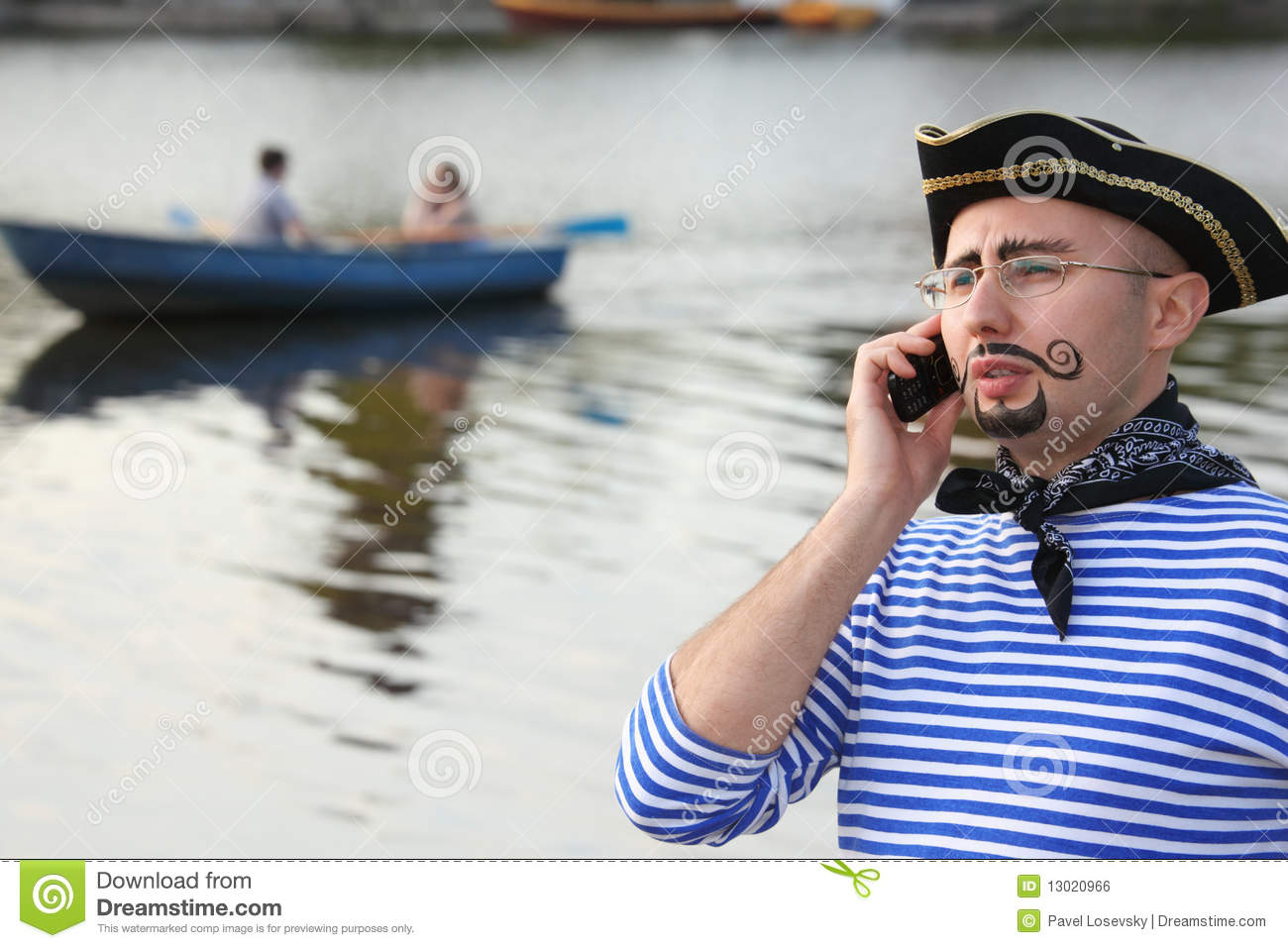Man in pirate suit is talking by the phone.