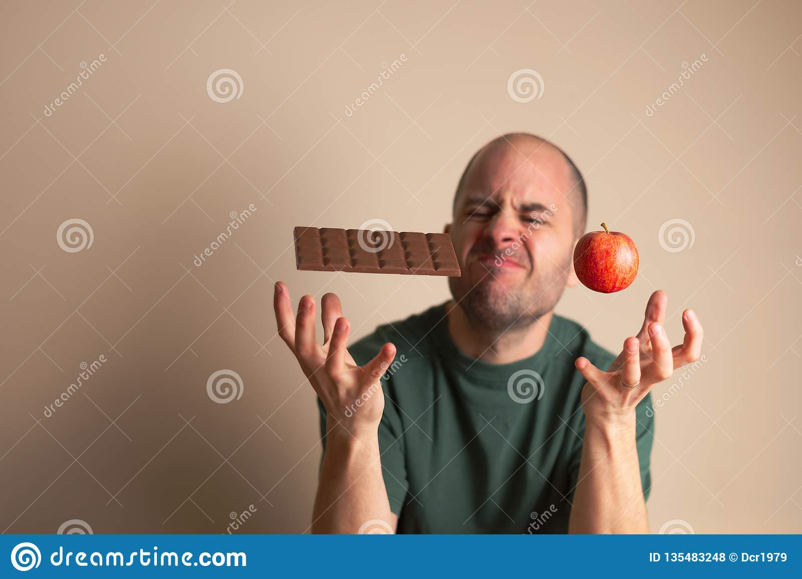 Man places one hand underneath a chocolate bar and the other underneath an apple