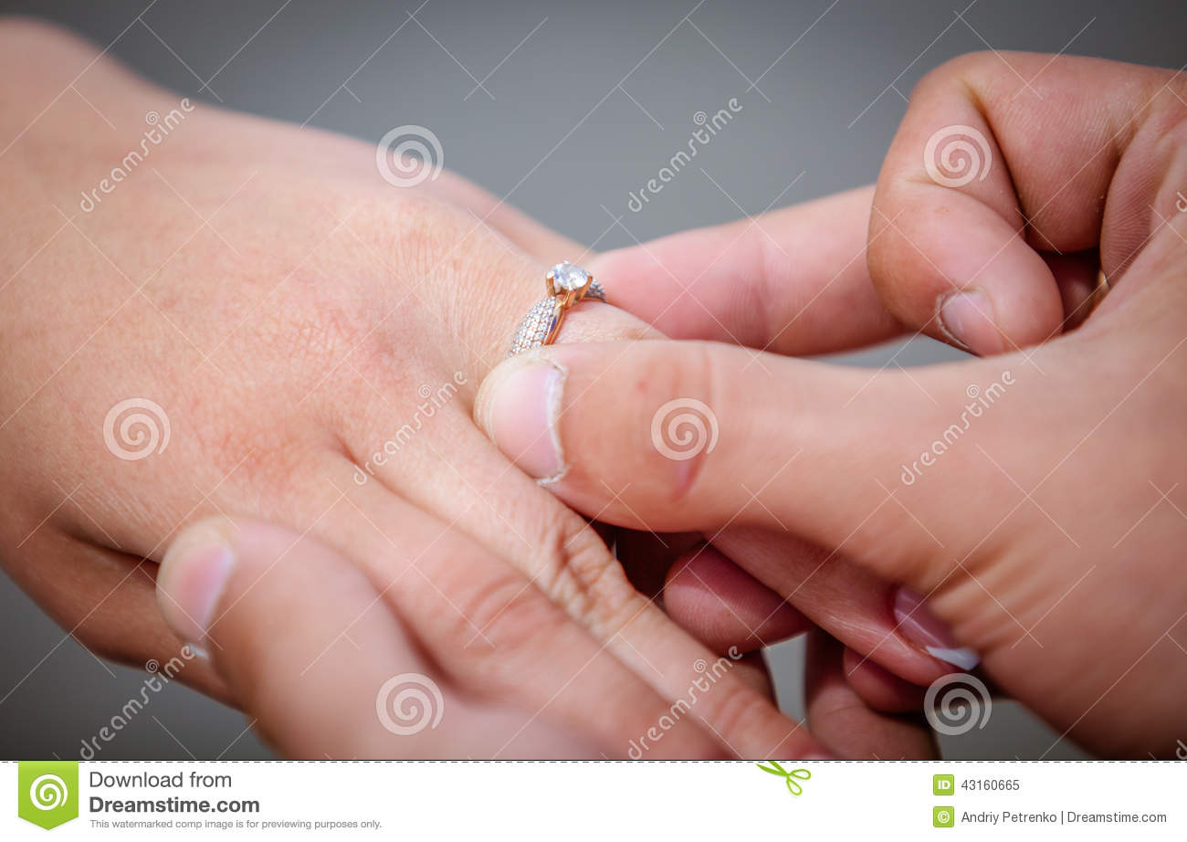 Man Placing A Diamond Engagement Ring On Finger Of His Fiance Stock ...