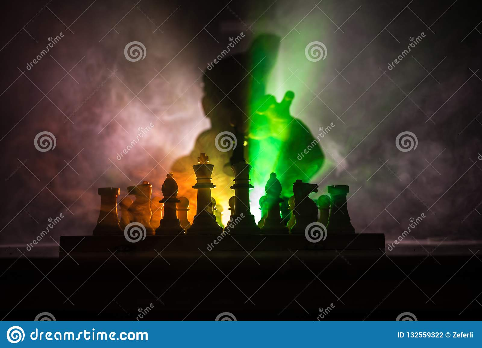Man playing chess. Scary blurred silhouette of a person at the chessboard with chess figures. Dark toned foggy background