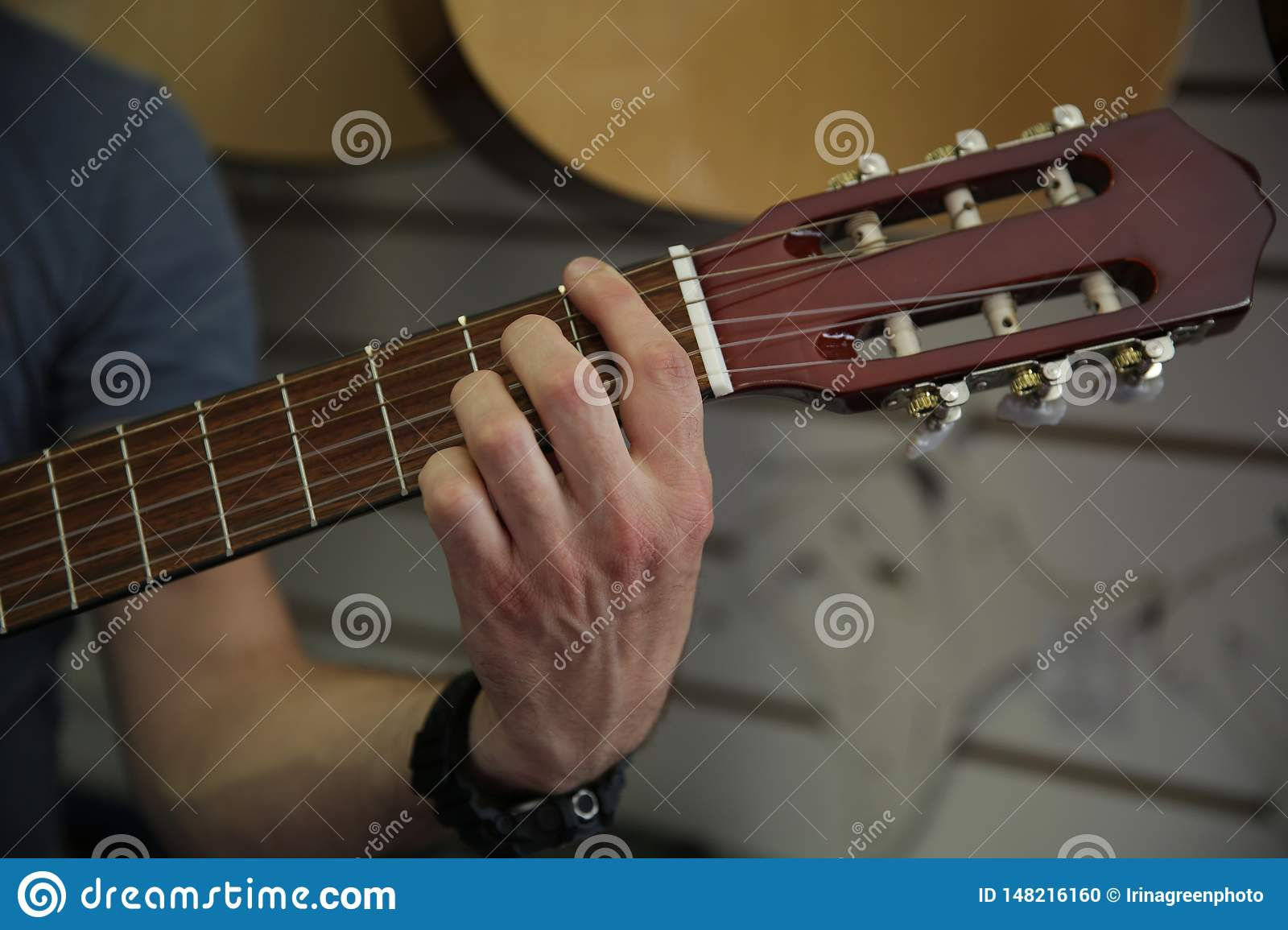 Man playing a classic guitar. Hand picks up the strings on the guitar.