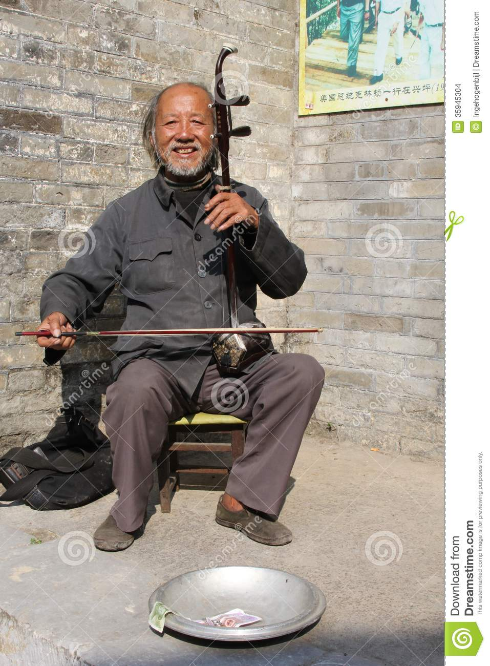A man is playing the traditional musical instrument which is called Erhu or Nanhu and sounds like a violin, China