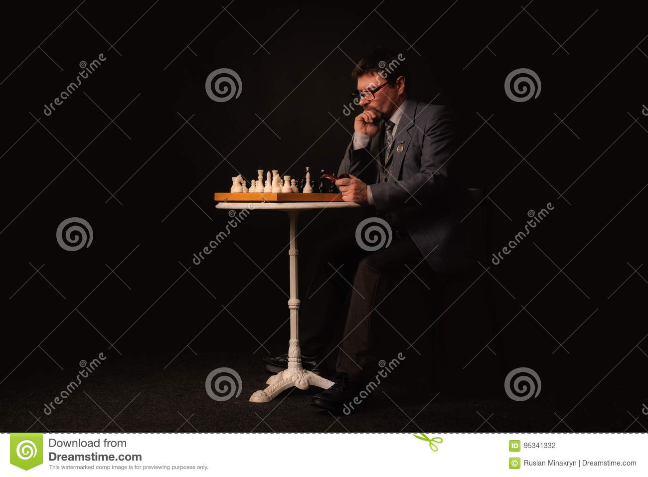 A man plays chess and smokes a pipe on a dark background