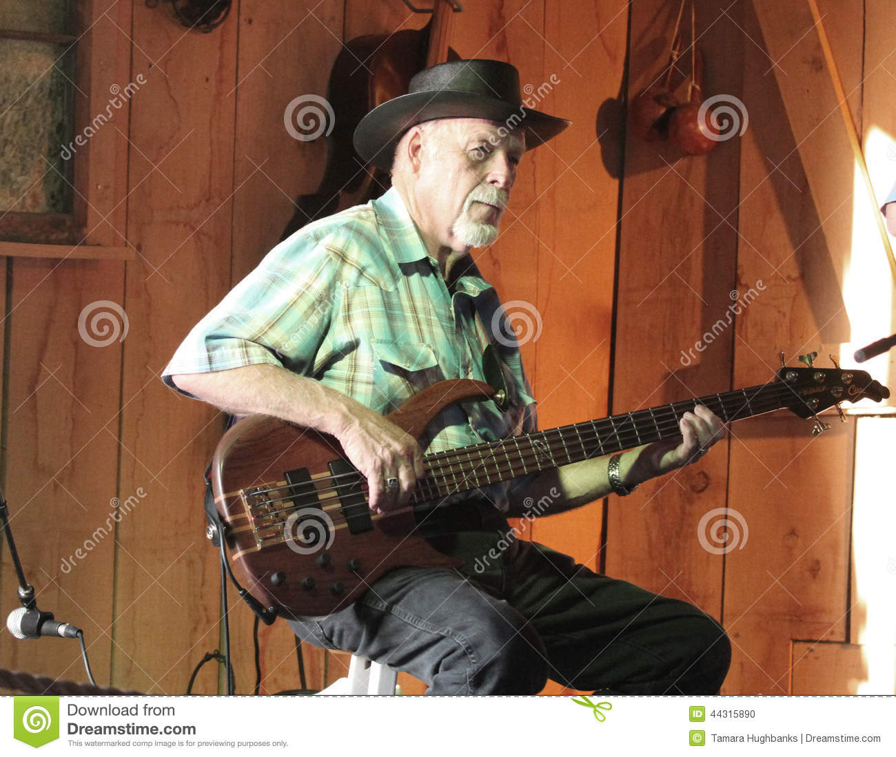 Man plays electric guitar in a barn during a festival