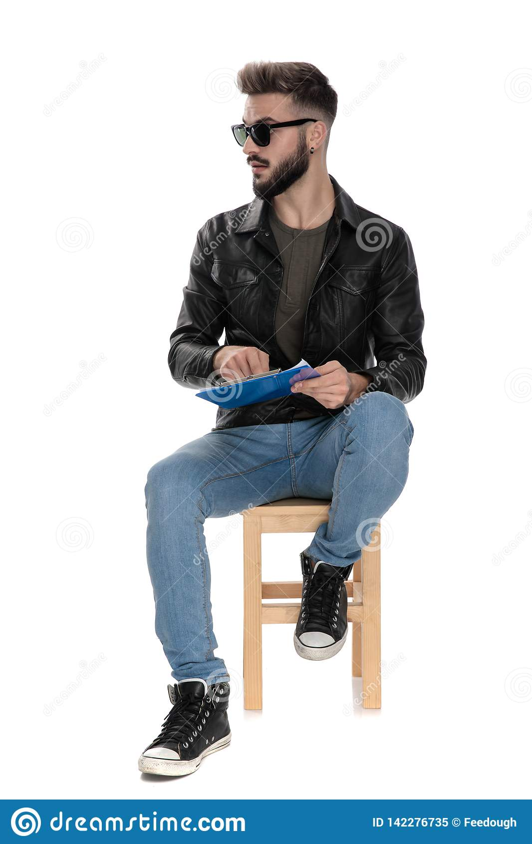 Man pointing his finger at blue folder while looking away