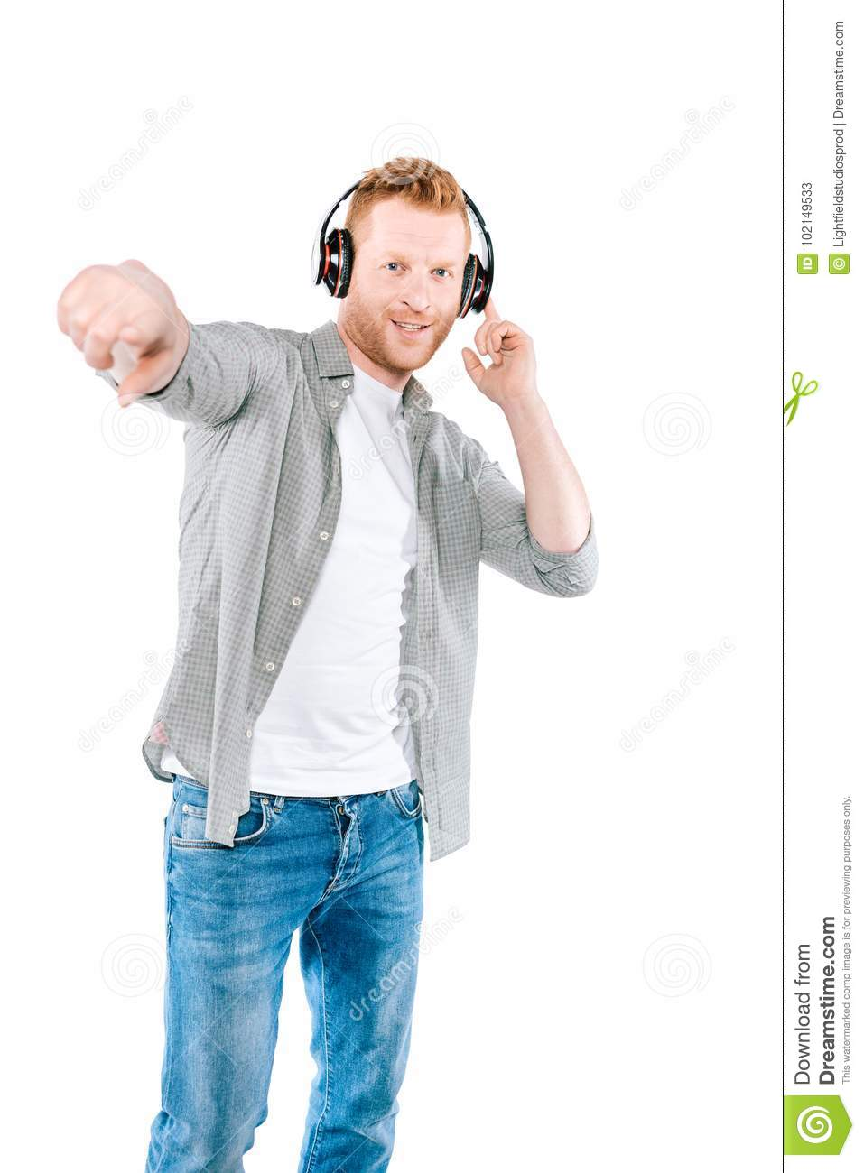 Handsome man pointing and listening music with headphones isolated on white