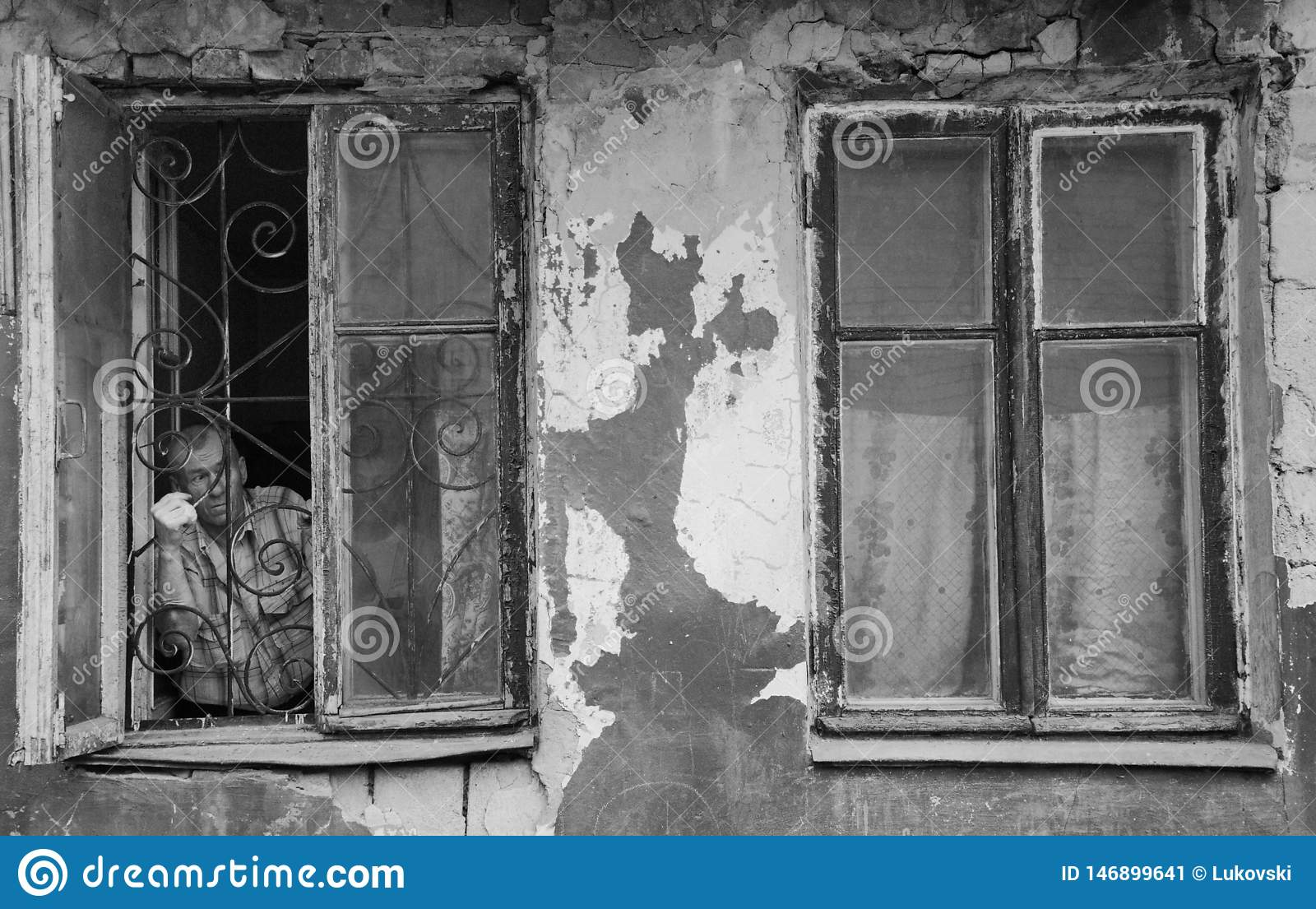 A man in a poor quarter looking out the window of an old house