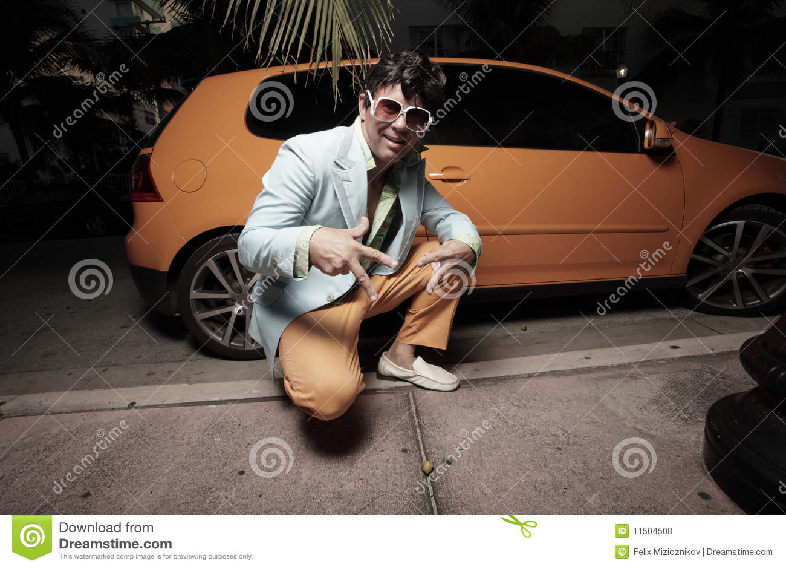 man posing by an orange sports car royalty free stock