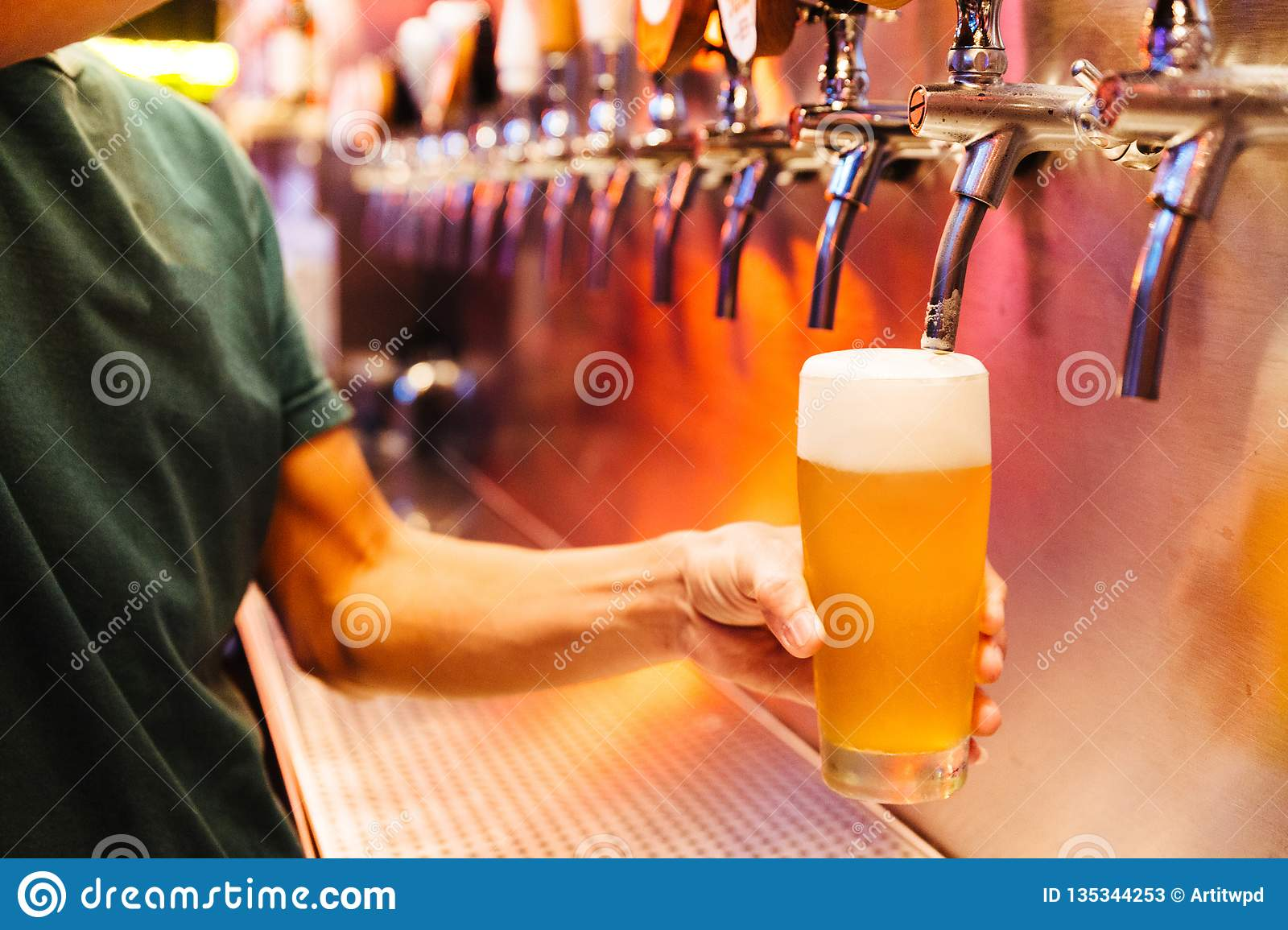 Man pouring craft beer from beer taps in frozen glass with froth. Selective focus. Alcohol concept. Vintage style. Beer craft