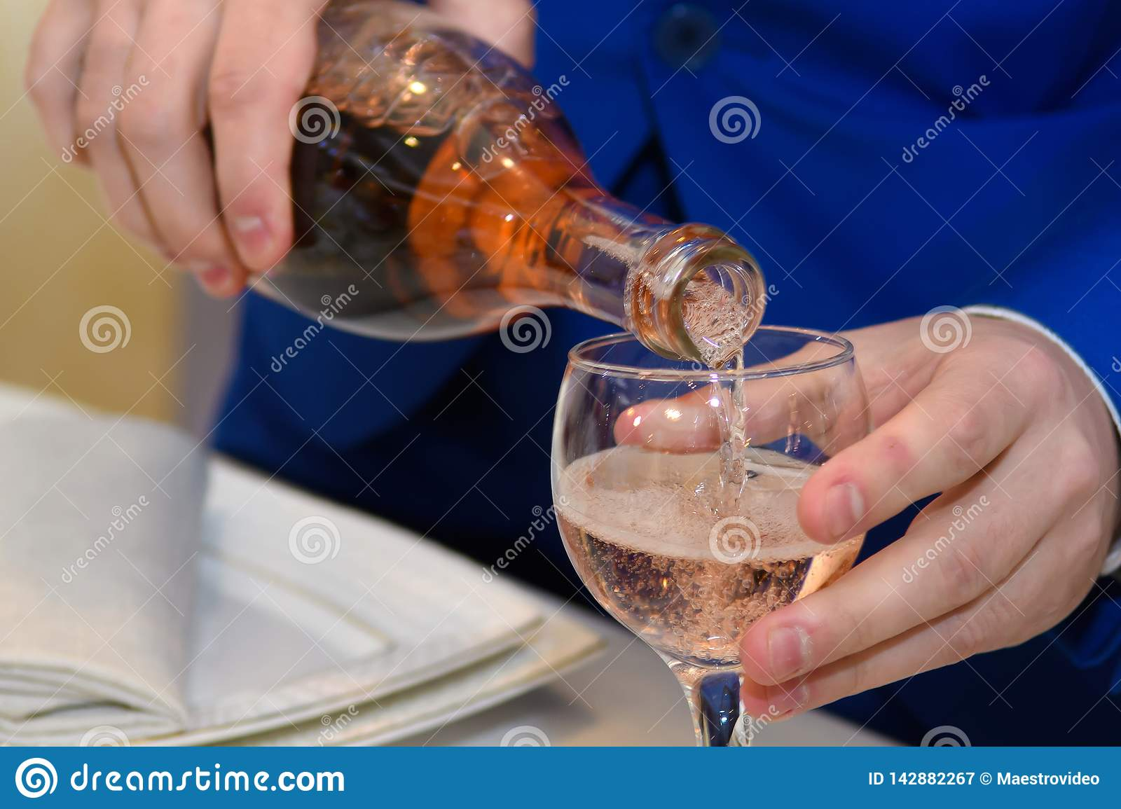 A man pours wine into a glass