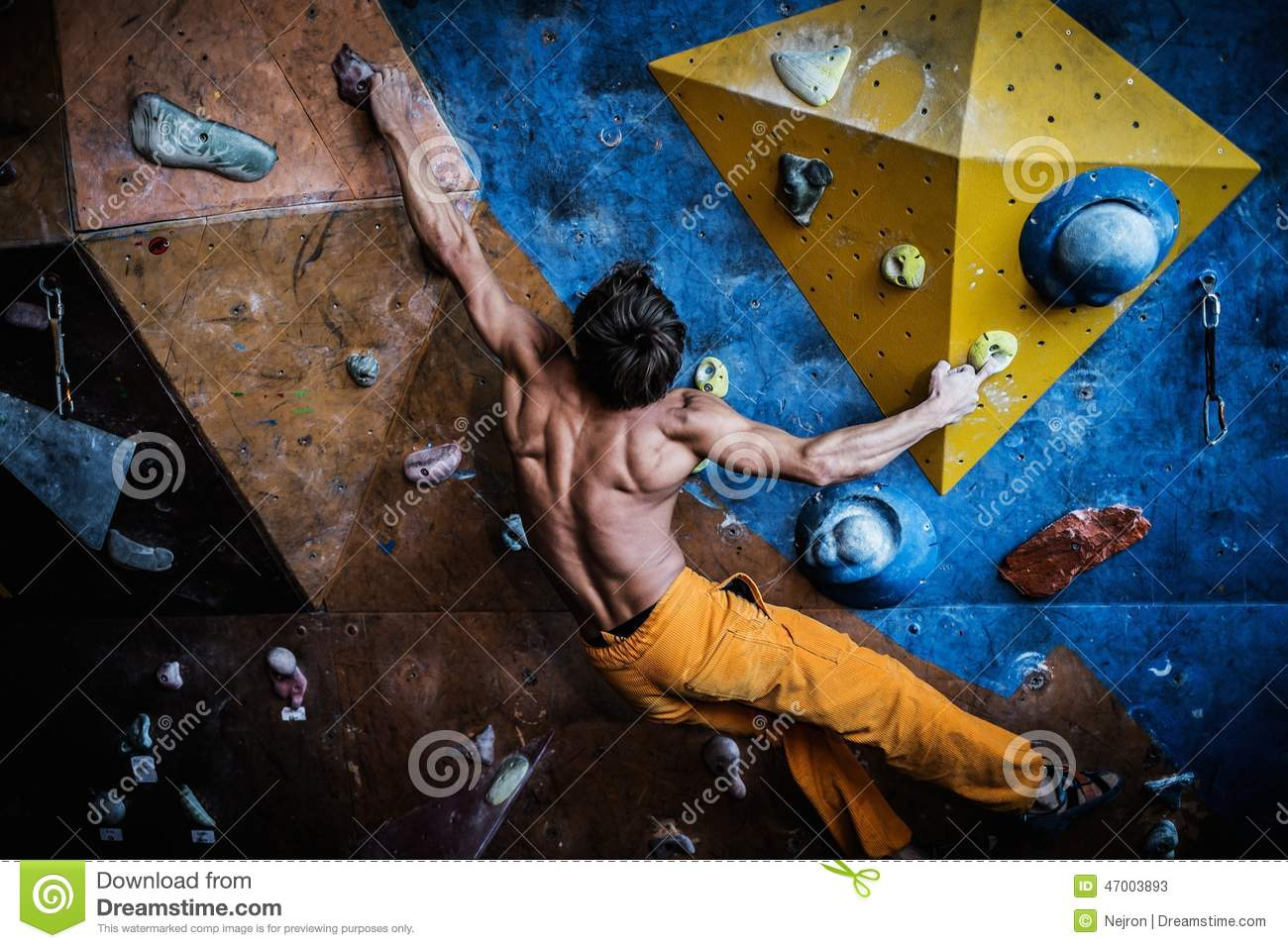Man practicing rock-climbing on a rock wall