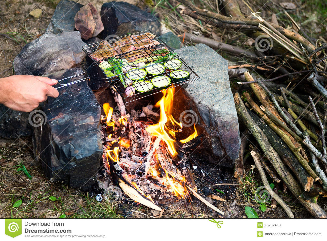 Man preparing dinner on campfire, adventure lifestyle camping vacation