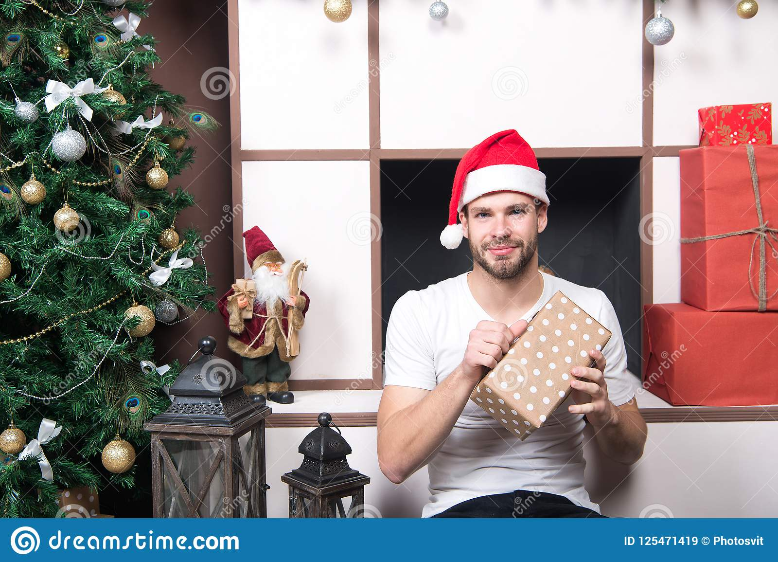 ad8f9f9defb4b Man with present box at Christmas tree. Macho in santa hat sit at  fireplace. xmas and new year gift. Boxing day concept. Winter holidays  preparation and ...