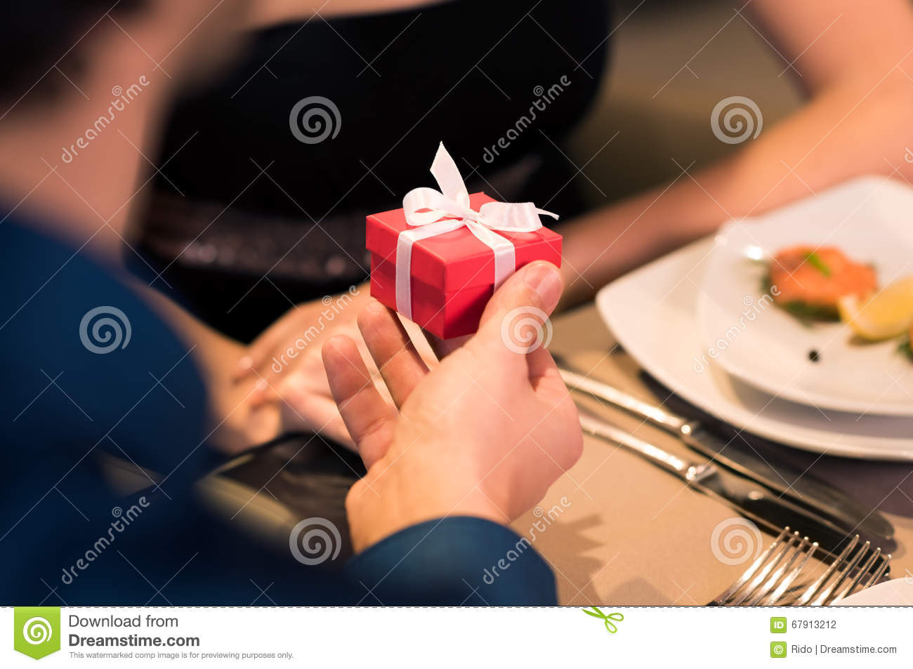 Young Men Gifting A Small Red Box To Woman Husband Give Present Wife On Her Birthday Close Up Of Boyfriend Hand Makes Marriage Proposal