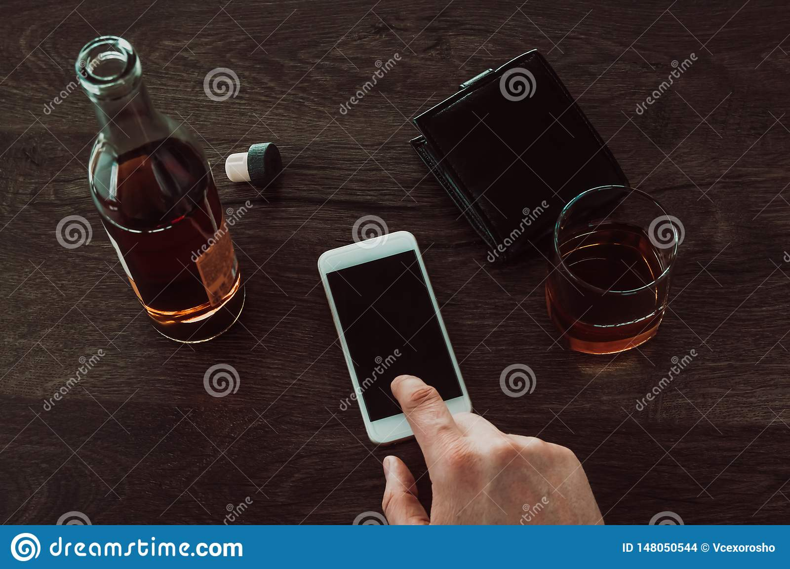 A man presses a finger on a mobile phone. Next on the table is a glass of whiskey, a bottle of whiskey and a purse