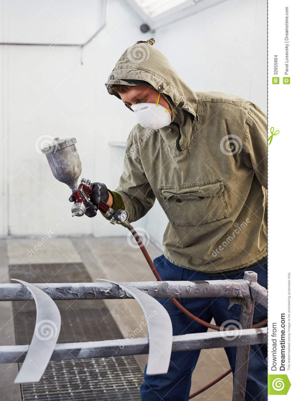 Man In Protective Clothes And Respirator Paints Car
