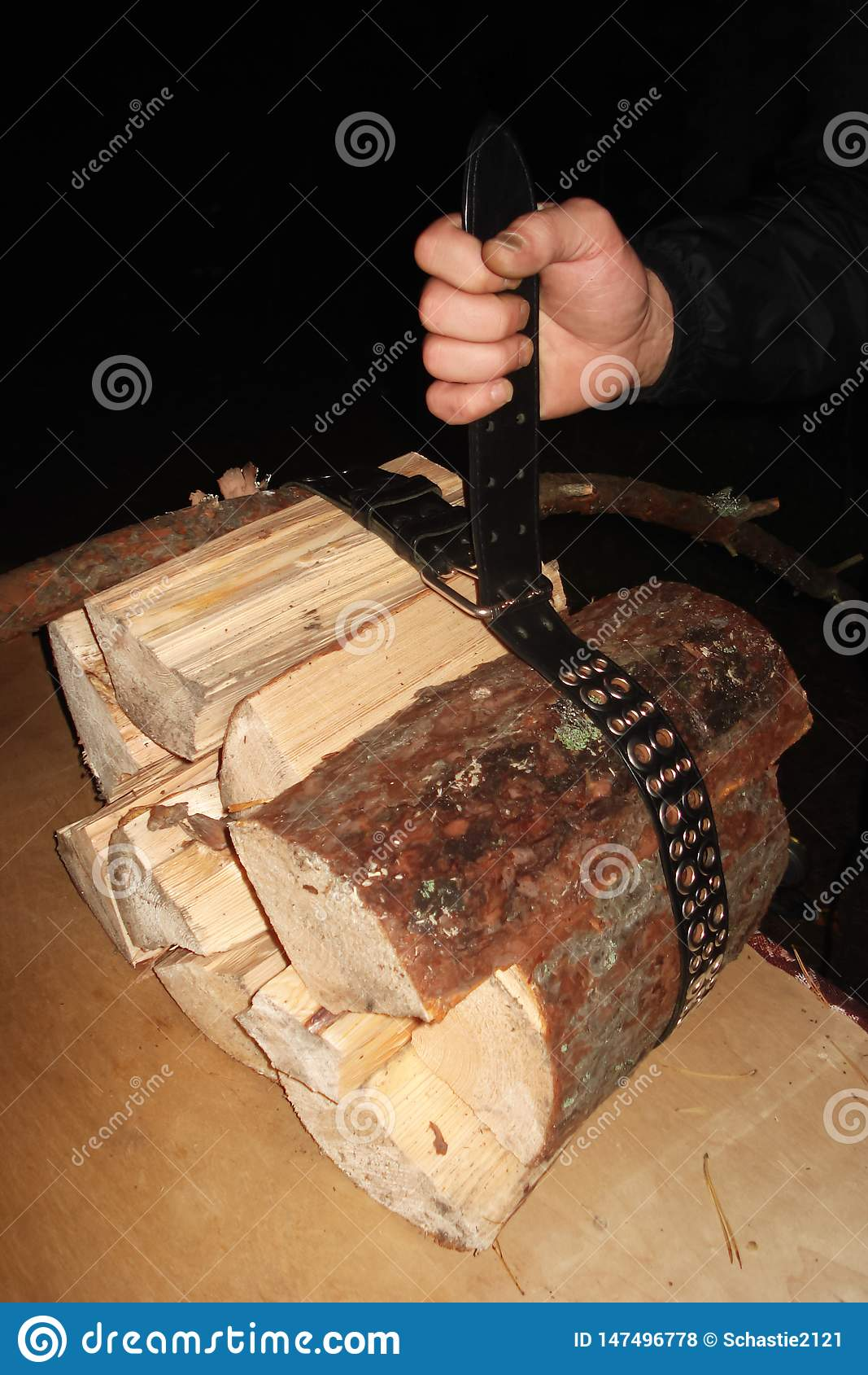 The man pulled the leather belt over the logs and holds them in his hand.