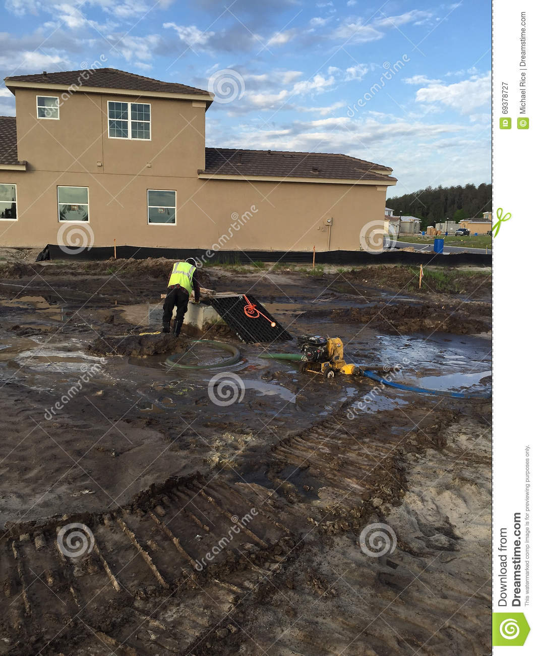 Man pumping water for underground work in dirt construction site royalty free stock photo sciox Gallery
