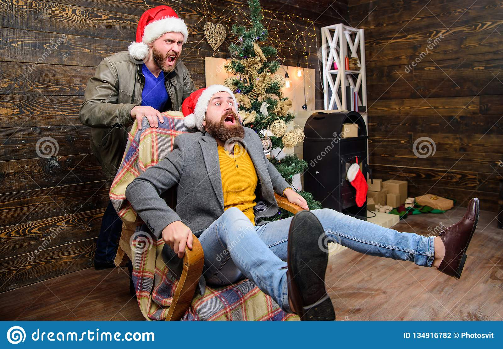 Man push armchair with friend. Cheerful men having fun at home. Christmas fun. You will never be bored if you have such