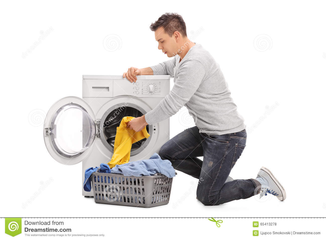 Clothes Being Washed ~ Man putting clothes in a washing machine stock photo