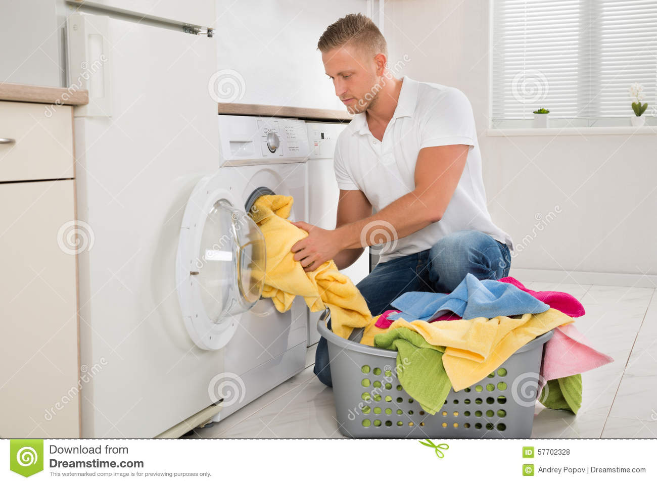 Man Putting Dirty Clothes Into The Washing Machine Stock
