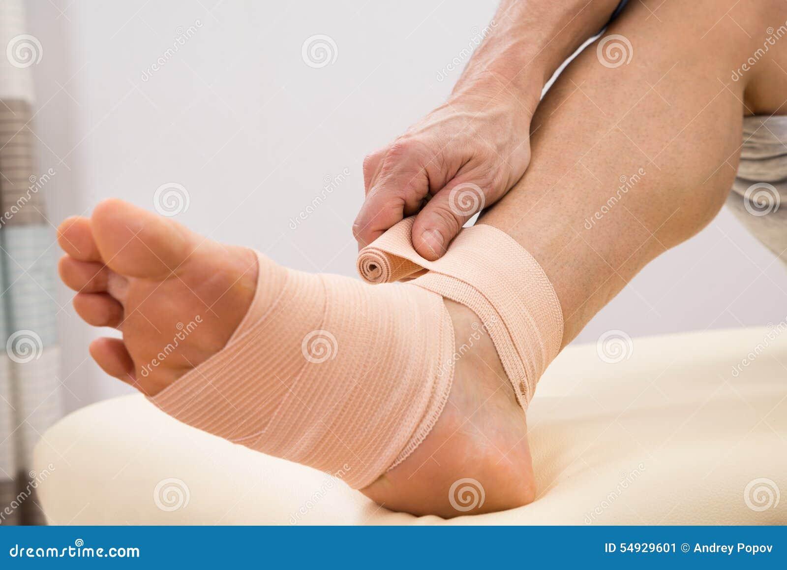 Man putting elastic bandage on foot
