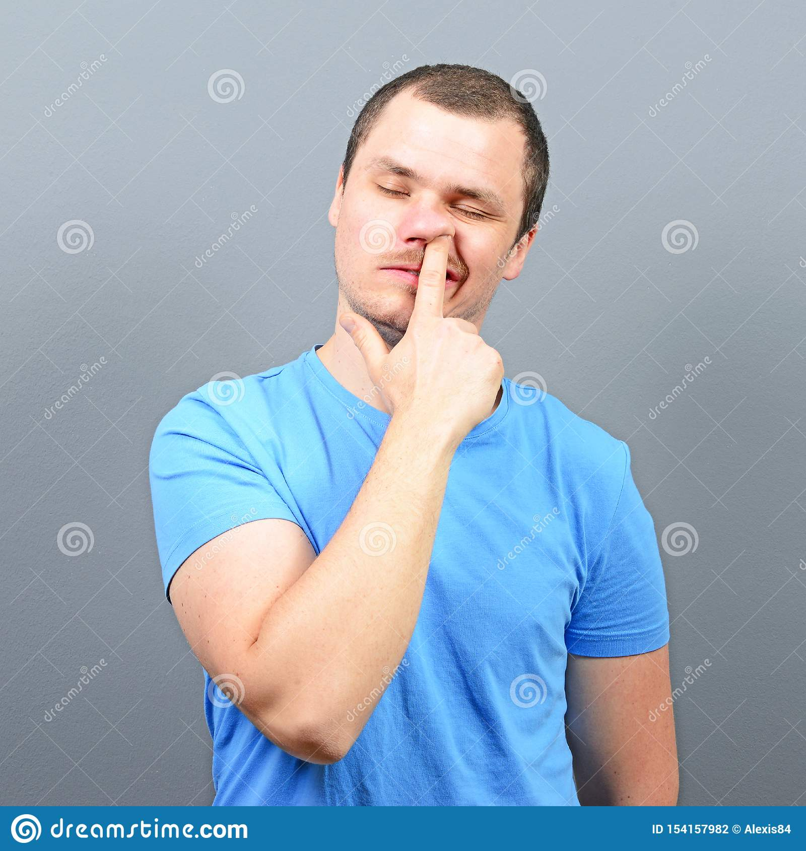 Man putting finger deep in his nose - Bad habit concept
