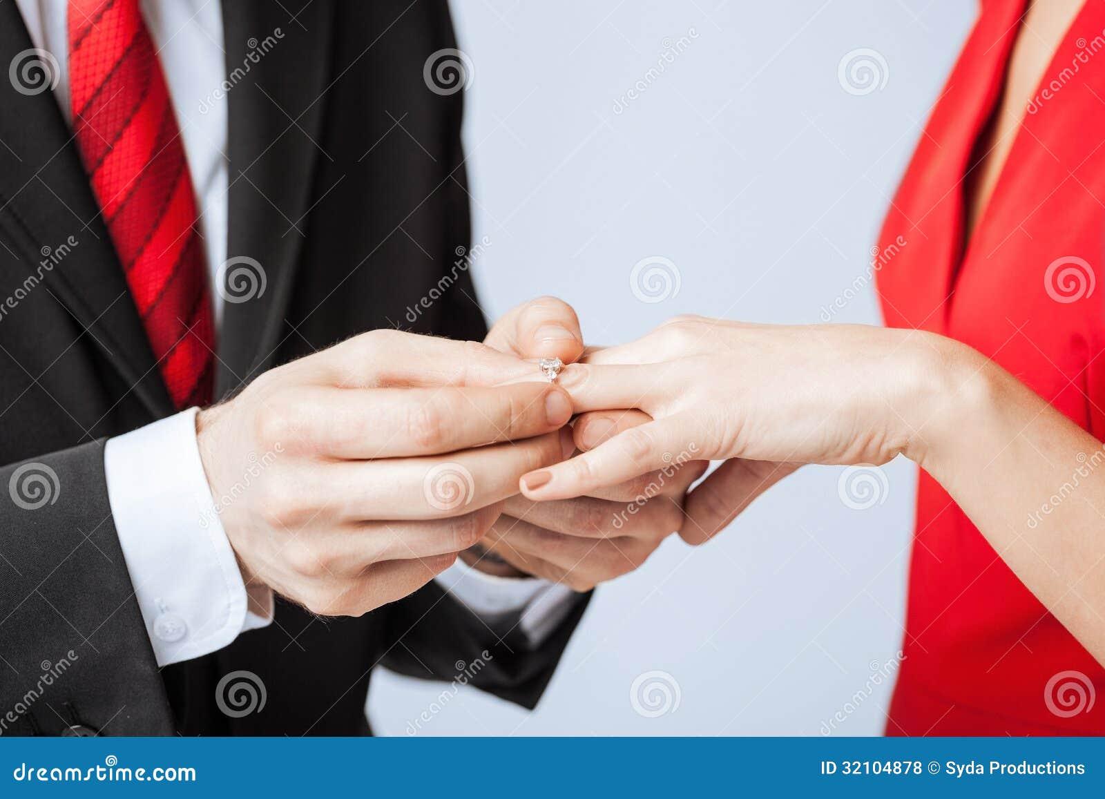 man putting wedding ring woman hand man wedding ring Man putting wedding ring on woman hand Royalty Free Stock Photos