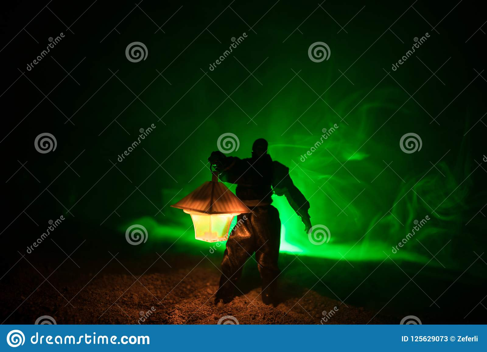 Man In Raincoat Coming From Dark Forest With Glowing Lantern