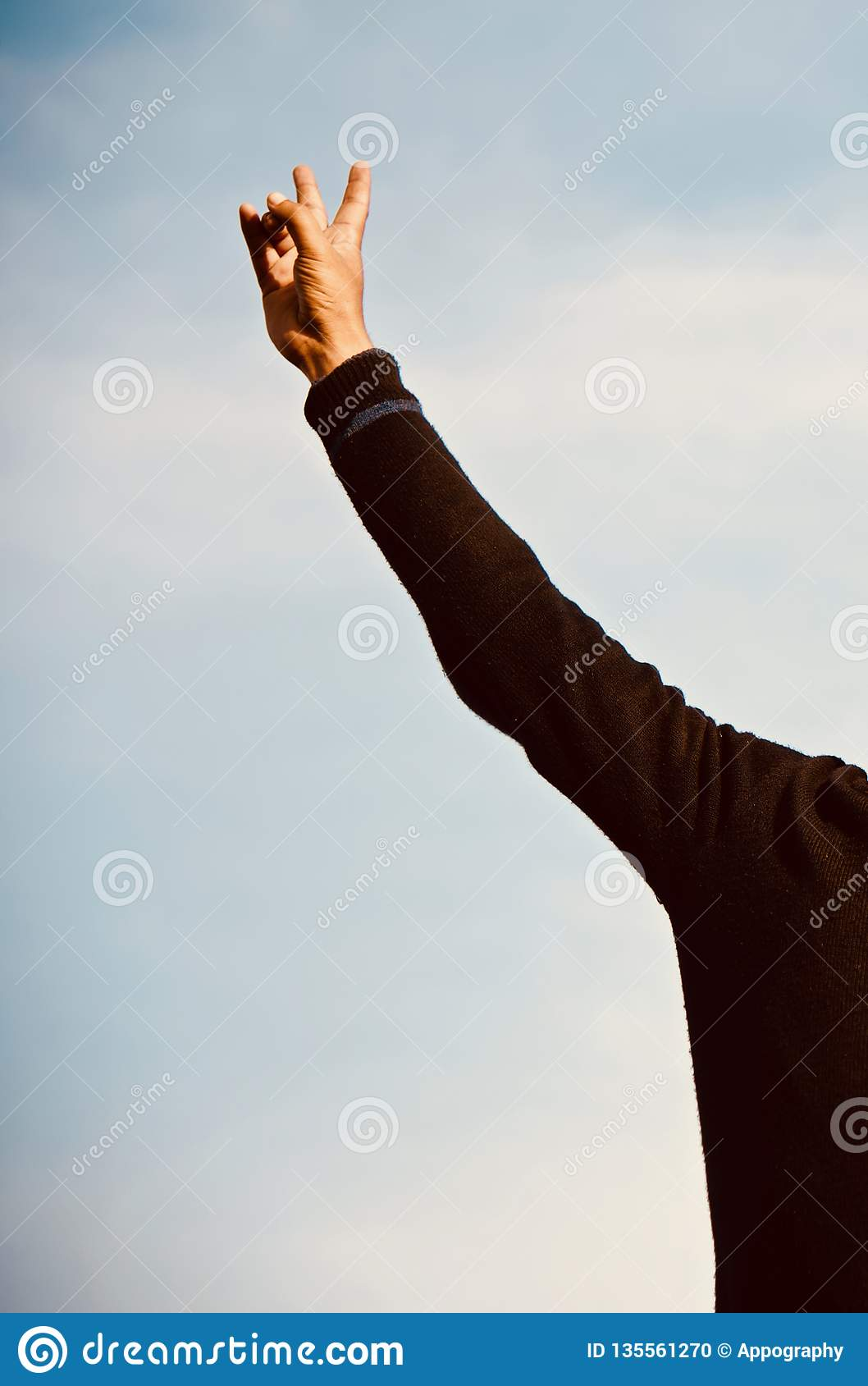 Man raising the right hands with sky background photo