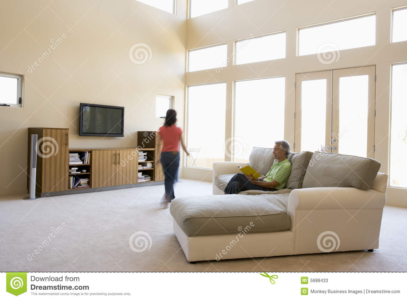 Man Living Room Man Reading Book In Living Room With Woman Walking Stock Photos