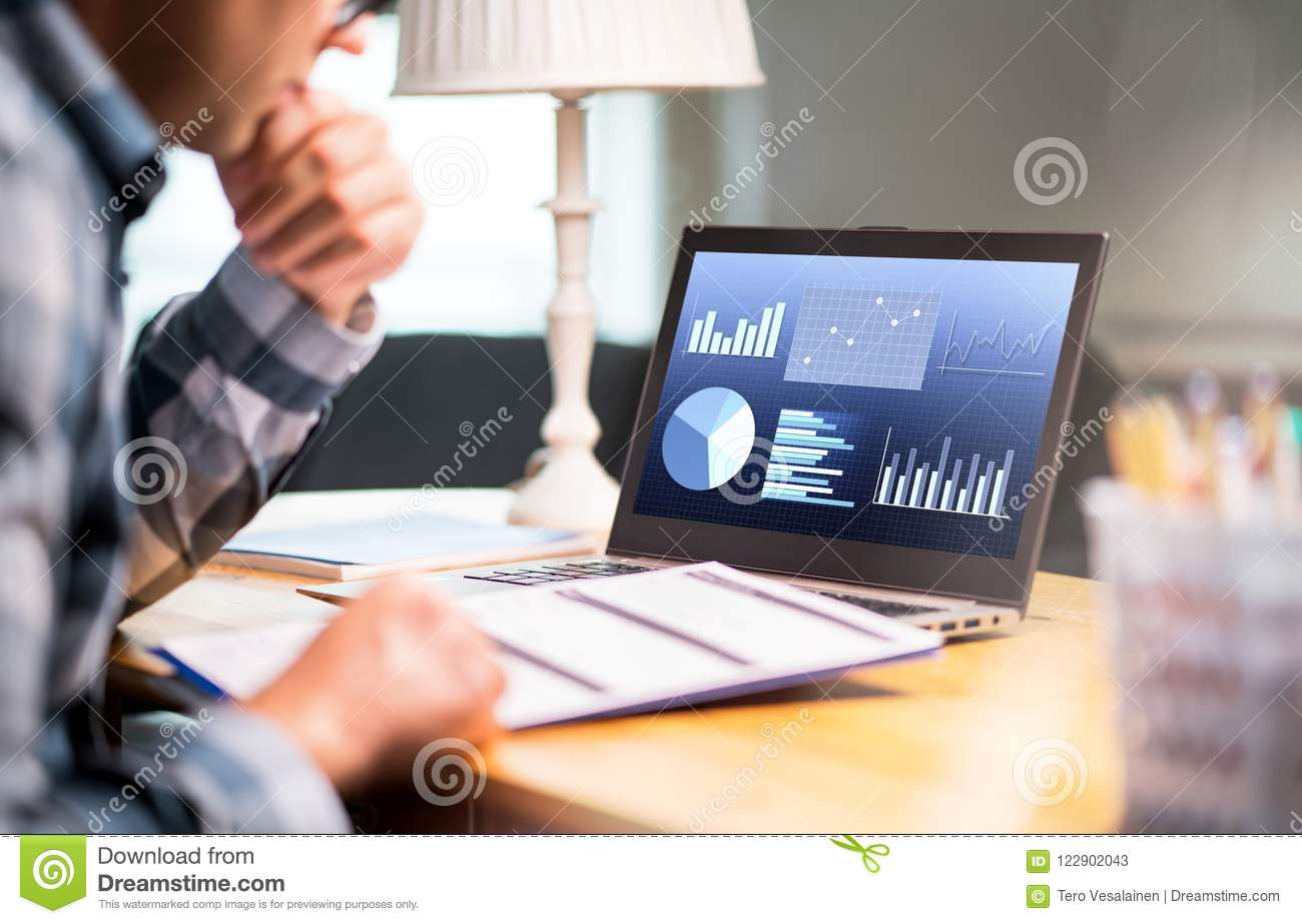 Man reading business report paper. Laptop with financial graphs